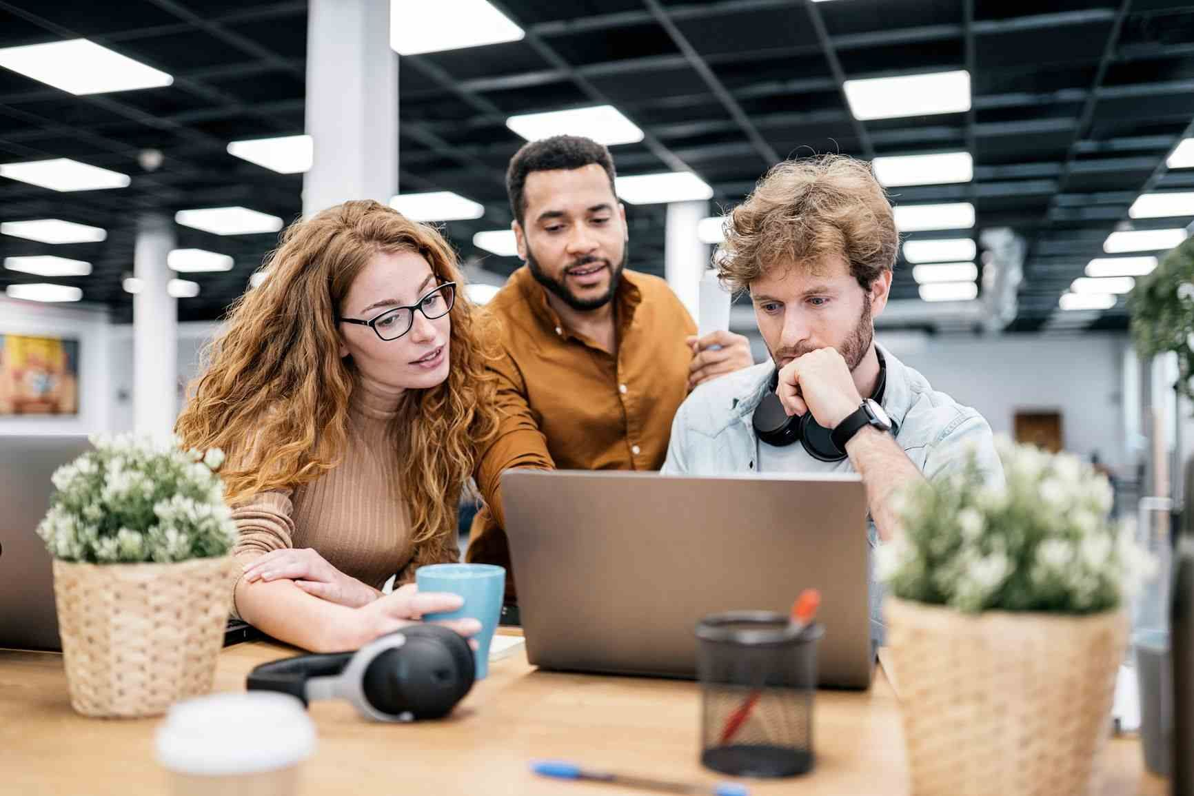 Three office workers looking at computer, trying to solve for recruiting bottlenecks
