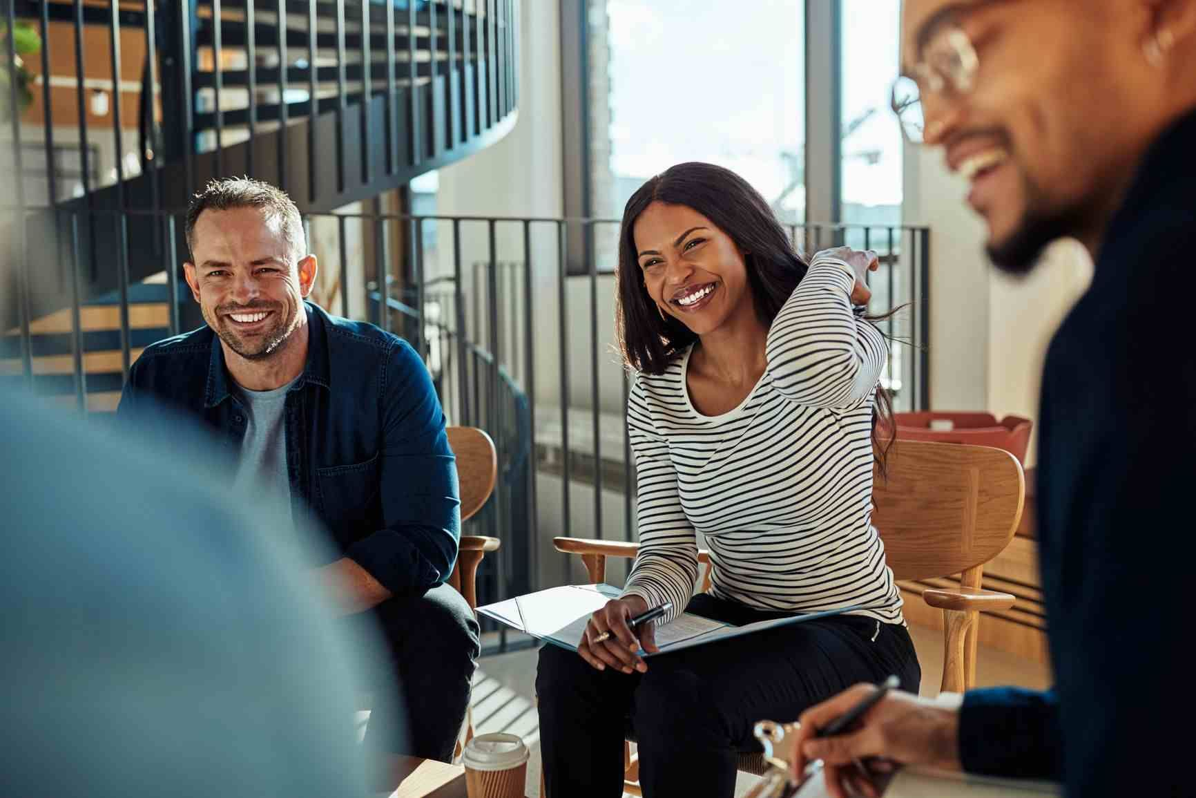 Diverse group of coworkers laugh together at the office