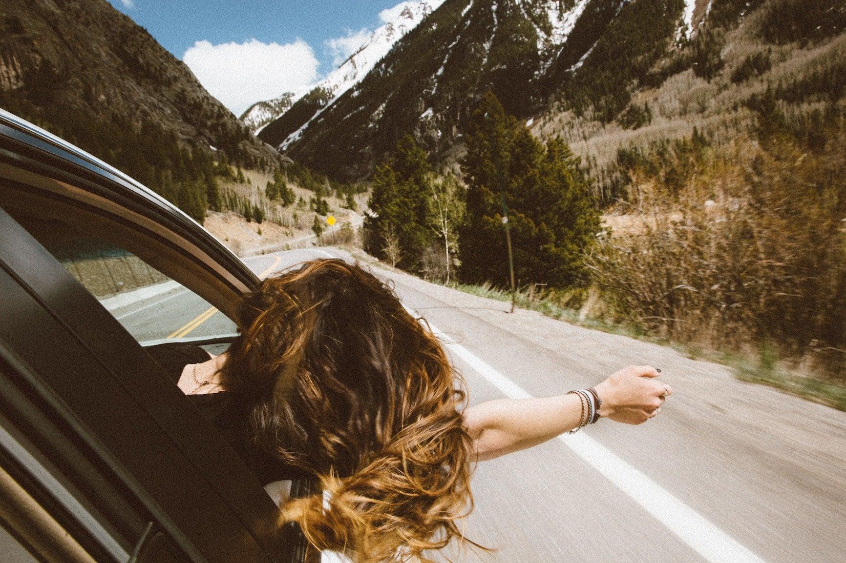 woman in car on road trip